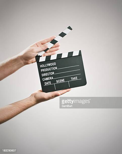 Two hands holding a clapperboard on a white background