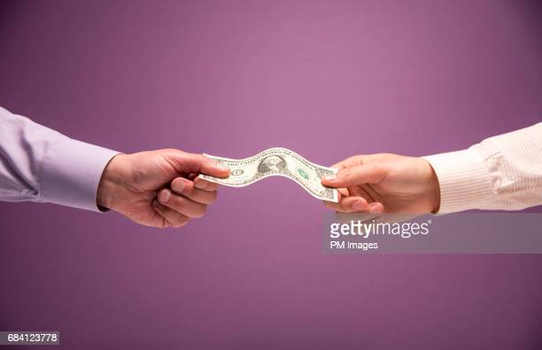 Two hands holding a US 1 dollar bill