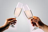 Two hands holding and toasting champagne