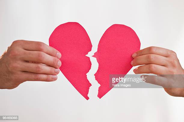 Two hands holding broken paper heart