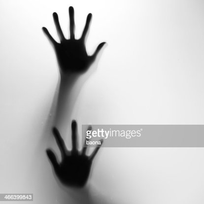Two hands in silhouette pressed against frosted glass