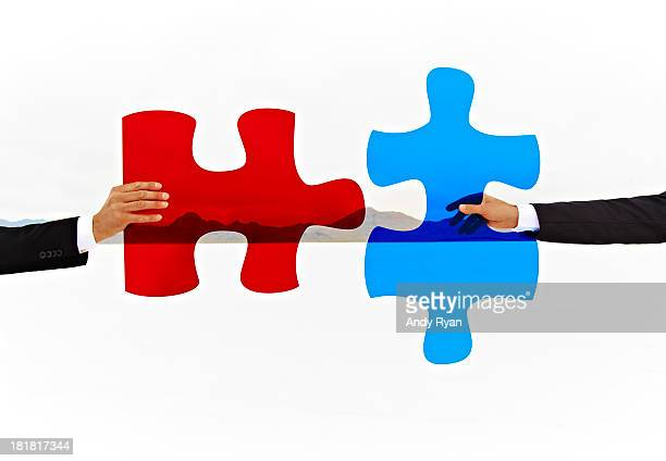 Two hands join colored puzzle pieces.