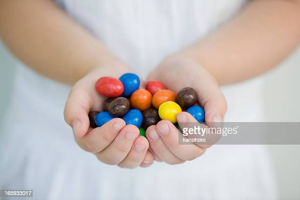 Two hands of a child holding colorful candies
