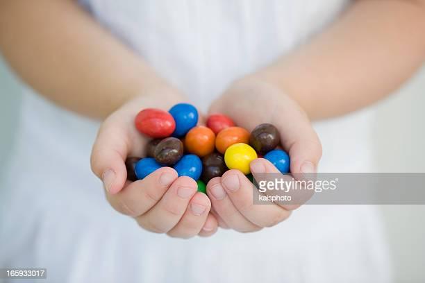 Deux mains d'un enfant tenant des bonbons colorés