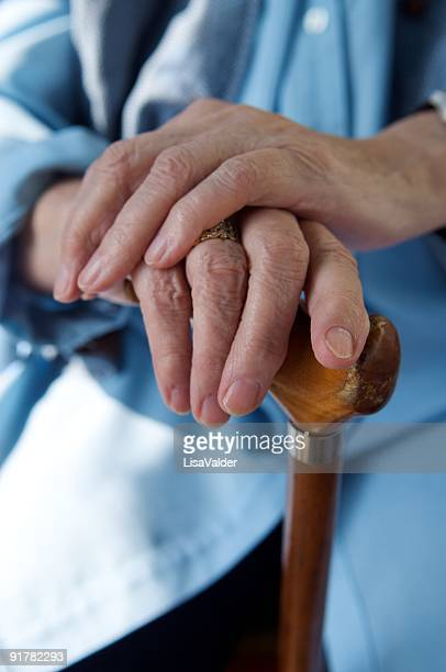 Two hands resting in a wooden cane