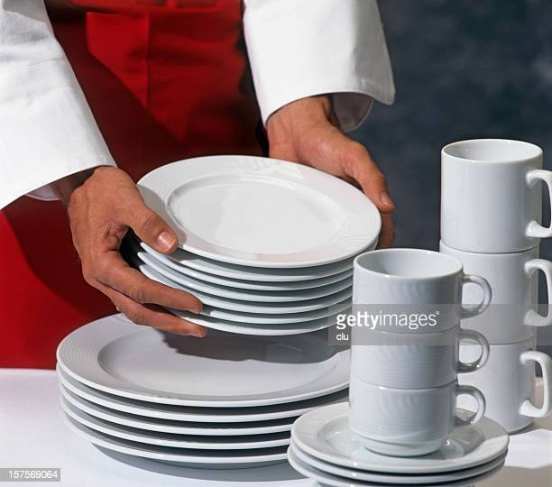 Two hands stacking plates and coffee cups