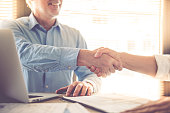 Cropped image of two handsome businessmen shaking their hands and smiling while working in office