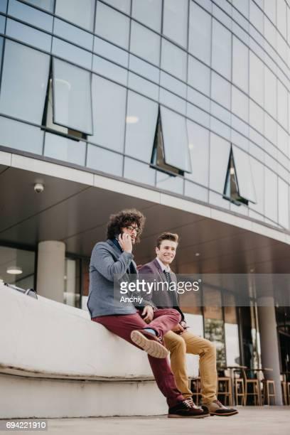 Deux collègues beau prennent une pause en face du centre d'affaires