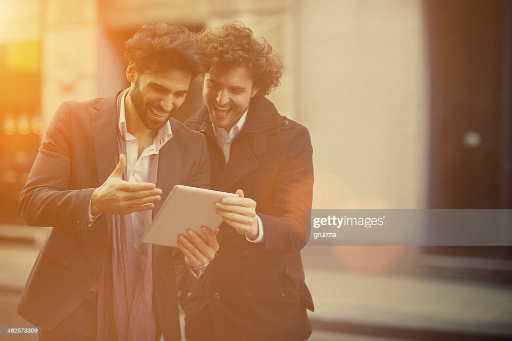 Two handsome guys watching on a digital tablet