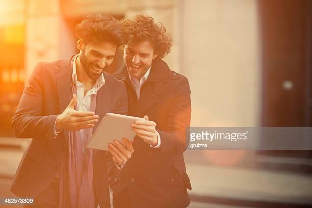 Dois rapazes bonito assistir a um tablet digital