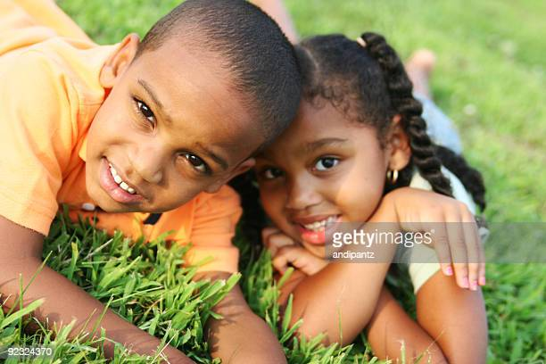 Two happy African American siblings laying in grass