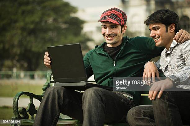 Two happy Asian young men sitting in park with laptop.