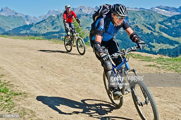 Two happy bikers flying down the track in the Alps