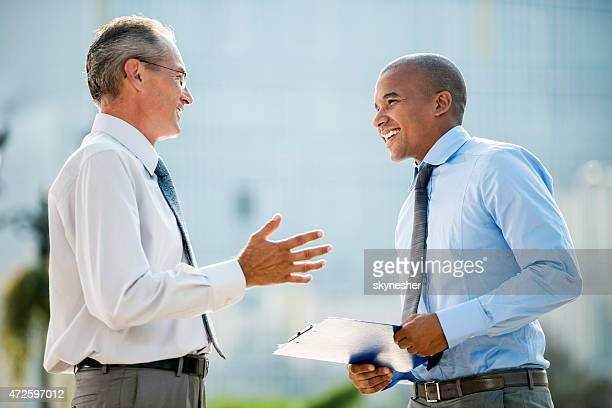 Two happy businessmen standing outdoors and discussing.