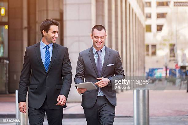 Two happy businessmen walking outdoors
