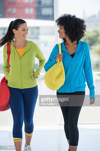 Two happy female friends carrying gym bags