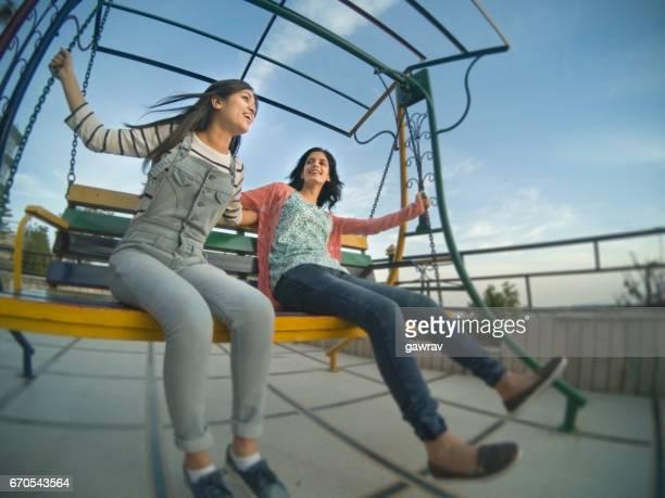 Two happy female friends having fun on swing.
