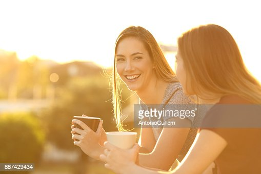 Two happy friends talking in a balcony at sunset : Stock Photo