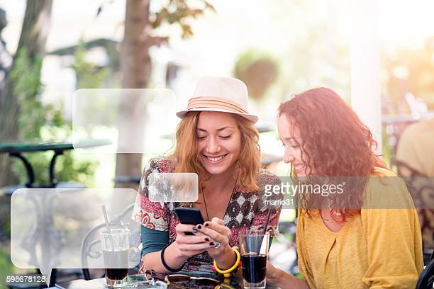Two happy friends texting in a cafe