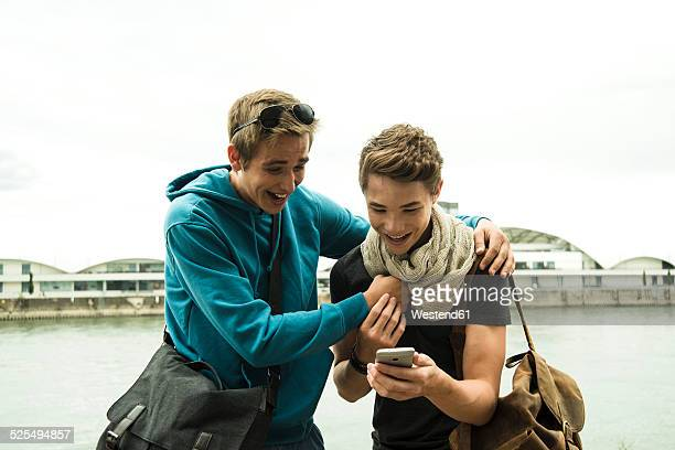 Two happy friends with cell phone by the riverside