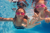 Close-up portrait of two smiling girls wearing pink goggles swimming under water of pool, pulling their hands to camera