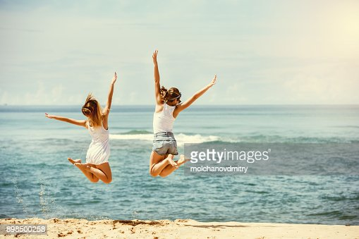 Two happy girls jumps at sunny beach : Foto stock