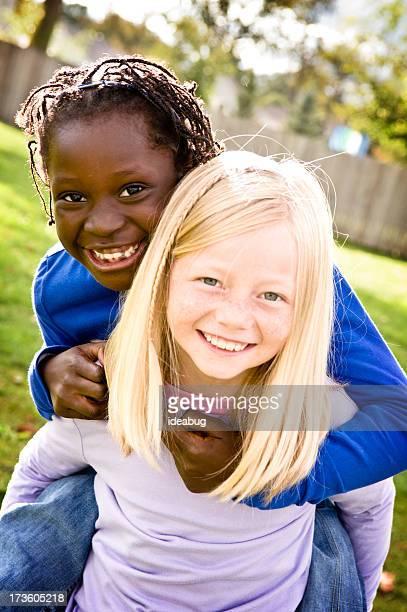 Zwei glückliche Mädchen Lächeln und Reiten draußen Huckepack nehmen
