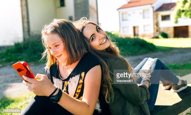 Two happy girls using their smartphones outdoors