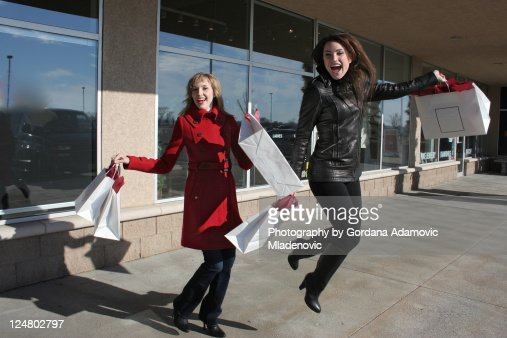 Two happy jumping shoppers : Stock Photo