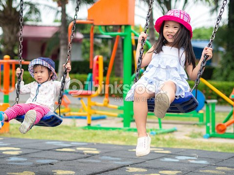 Two Happy little girls playing swing at the playground. Happy, Family, Sister Concept