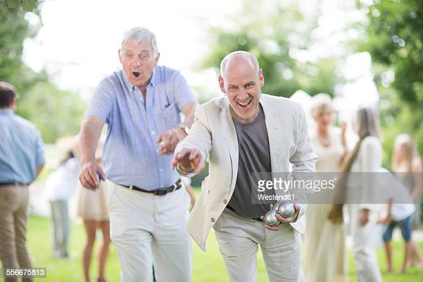 Two happy men playing boules in park