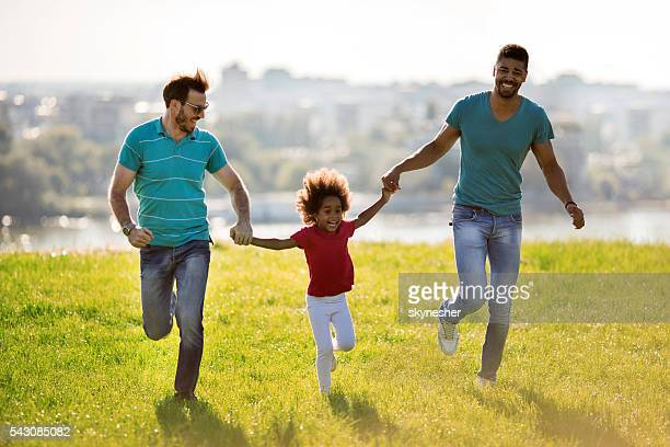 Two happy men running with African American little girl outdoors.