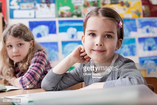 Two happy school girls (6-7) sitting in classroom : Foto de stock