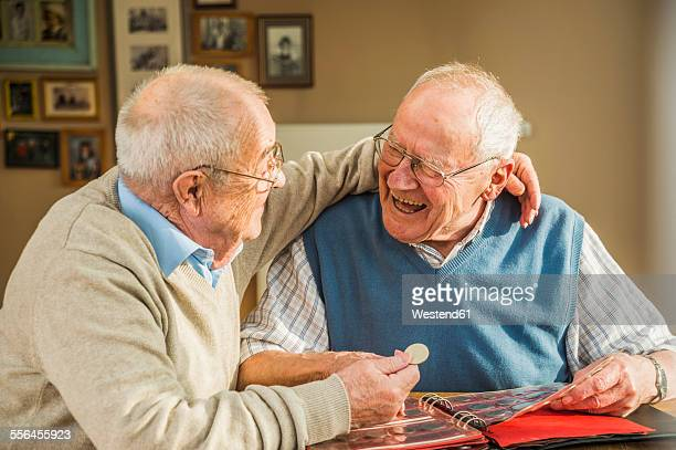 Two happy senior friends with coin album