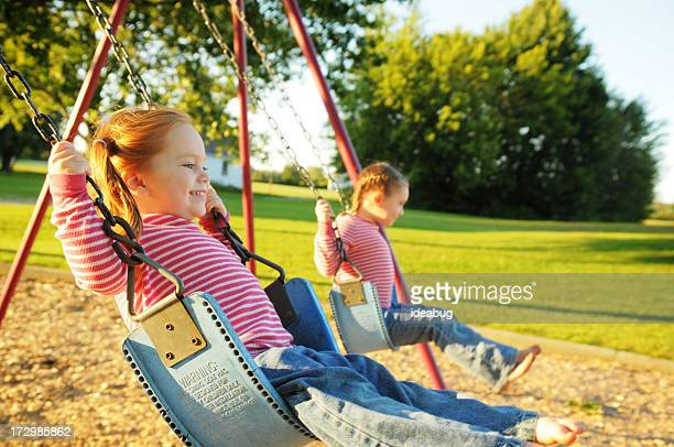 Two Happy Sisters Swinging Together