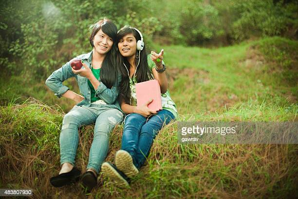 Two happy teenage girls from different ethnicity together in nature.