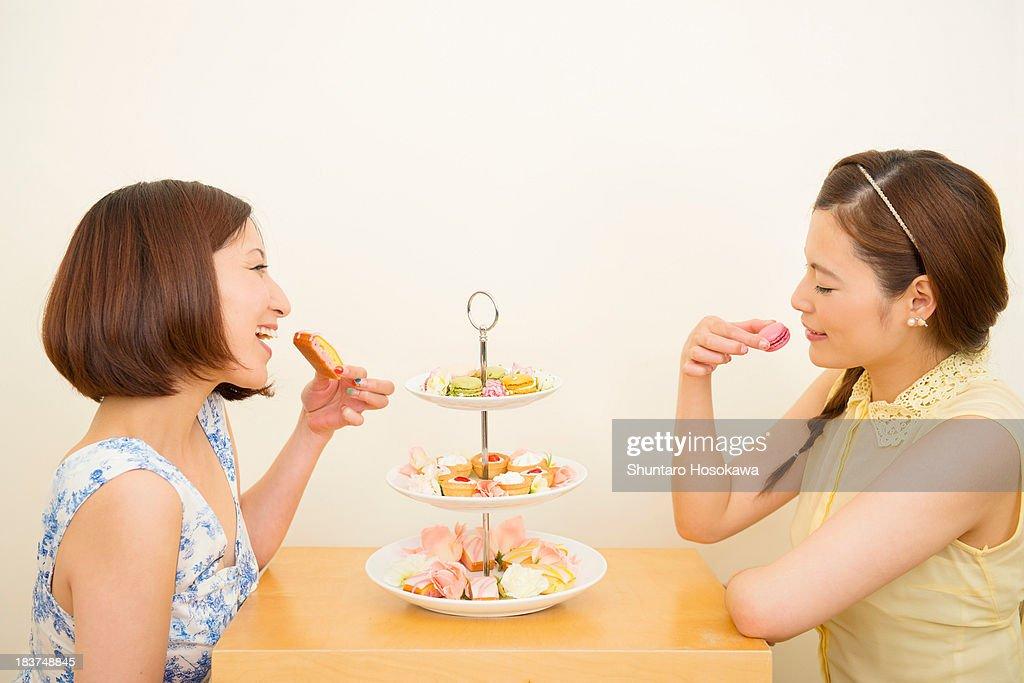 Two happy women enjoying dessert from three tiered cake stand