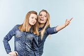 Friendship, human relations concept. Two happy women friends or sisters wearing jeans shirts pointing somewhere.
