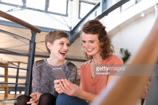 Two happy women in modern office sharing cell phone