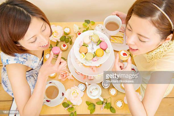 Two happy women indulging in sweet cakes