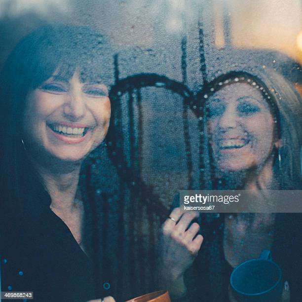 Zwei glückliche Frauen Lachen Hinter dem Fenster