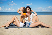 Side portrait of two happy women on beach using suntan oil