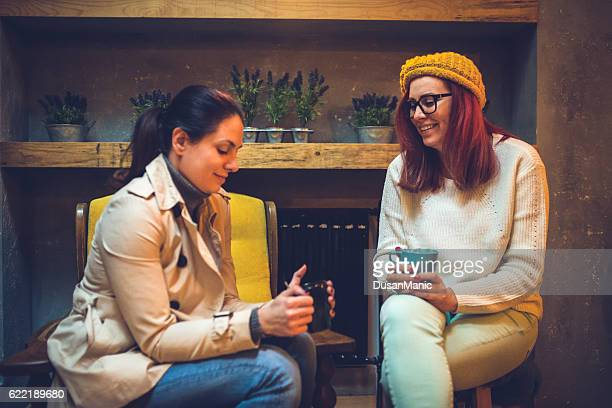 Two happy young female friends with coffee cups