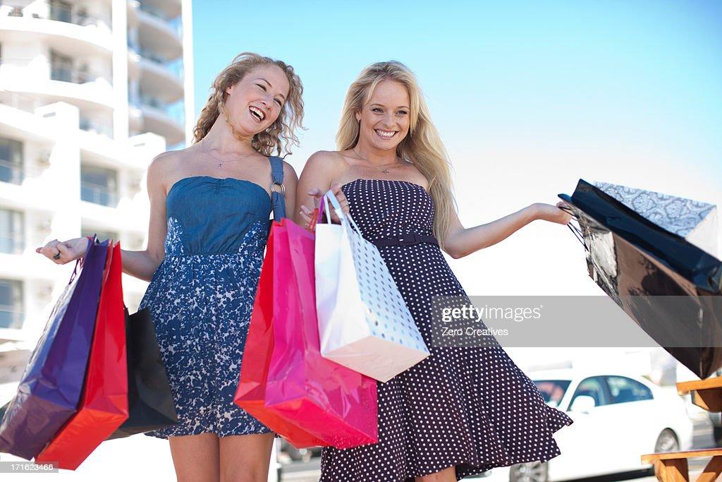 Two happy young women carrying shopping bags : Stock Photo