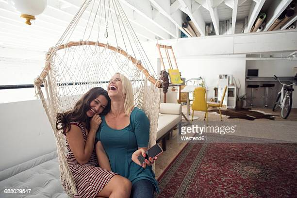 Two happy young women in hammock with cell phone
