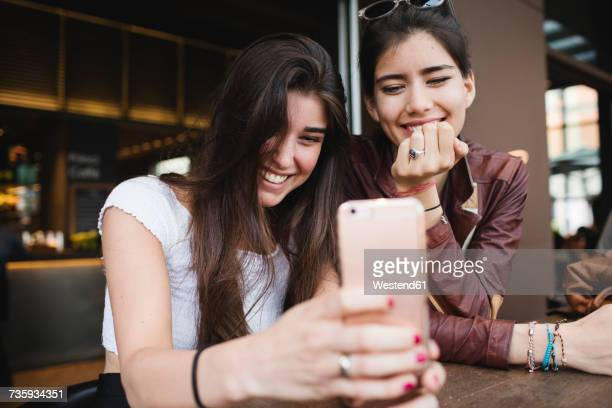 Two happy young women looking at cell phone in a bar