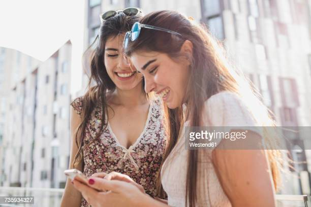 Two happy young women looking at cell phone in the city
