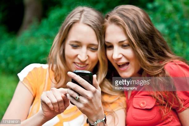 Duas mulheres jovens, olhando feliz e sorridente com o Smartphone