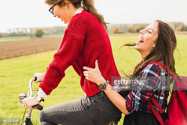 Two happy young women sharing a bicycle in rural landscape