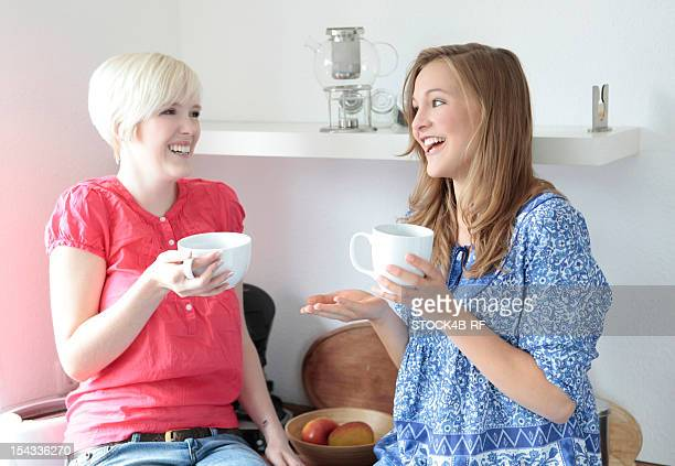 Two happy young women talking in kitchen